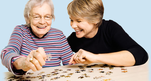 Senior playing puzzel with a Caregiver
